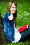 Estudiante femenino con los pulgares para arriba Fotografía de archivo libre de regalías