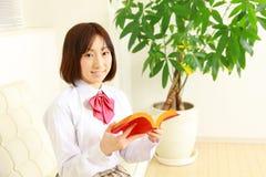 Estudiante femenino de la High School secundaria con un libro Foto de archivo