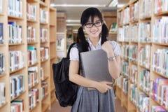 Estudiante femenino de la High School secundaria en biblioteca Fotografía de archivo libre de regalías