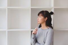 estudiante femenino del adolescente de la muchacha asiática que piensa algo al lado de abucheo Fotos de archivo
