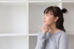 estudiante femenino del adolescente de la muchacha asiática que piensa algo al lado de abucheo Imagenes de archivo