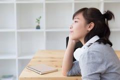 estudiante femenino del adolescente de la muchacha asiática que piensa algo al lado de BO Imagen de archivo