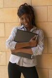 Estudiante femenino del afroamericano joven con la computadora portátil Fotografía de archivo