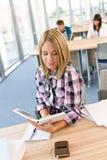 Estudiante femenino feliz con el libro en sala de clase Imagen de archivo libre de regalías