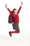 Estudiante femenino feliz en el uniforme que salta en aire Foto de archivo