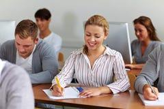 Estudiante femenino feliz que toma notas Imagenes de archivo