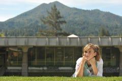 Estudiante femenino hermoso joven que pone en hierba Foto de archivo