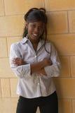 Estudiante femenino joven sonriente contra la pared de ladrillo foto de archivo libre de regalías