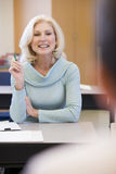 Estudiante femenino maduro que levanta la mano en clase Imagen de archivo