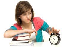 Estudiante femenino que apaga el reloj de alarma Imagen de archivo