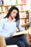 Estudiante femenino que lee un libro Fotografía de archivo libre de regalías