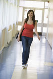 Estudiante femenino que recorre abajo del pasillo de la universidad Imágenes de archivo libres de regalías