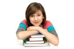 Estudiante femenino que se inclina en bookslaptop Imagen de archivo libre de regalías