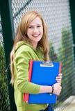 Estudiante femenino que se inclina en la cerca Imagen de archivo libre de regalías