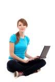 Estudiante femenino que se sienta con la computadora portátil. Aislado Fotos de archivo libres de regalías