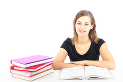 Estudiante femenino que se sienta en un escritorio con los libros Foto de archivo