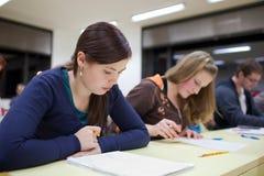 Estudiante femenino que se sienta en una sala de clase Imagenes de archivo