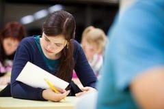 Estudiante femenino que se sienta en una sala de clase Fotos de archivo libres de regalías