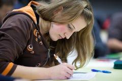 Estudiante femenino que se sienta en una sala de clase Foto de archivo