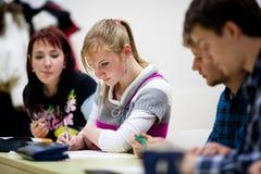 Estudiante femenino que se sienta en una sala de clase Imagen de archivo
