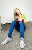 Estudiante femenino que se sienta por la pared Imagenes de archivo