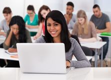 Estudiante femenino que usa la computadora portátil fotografía de archivo libre de regalías