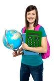 Estudiante femenino sonriente que sostiene una calculadora, globo Imágenes de archivo libres de regalías