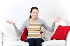 Estudiante femenino sonriente que sostiene una pila de libros. Fotografía de archivo