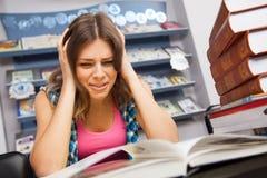 Estudiante femenino tensionado en una biblioteca Fotografía de archivo libre de regalías
