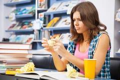 Estudiante femenino tensionado en una biblioteca Imagenes de archivo