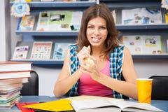 Estudiante femenino tensionado en una biblioteca Imágenes de archivo libres de regalías