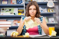 Estudiante femenino tensionado en una biblioteca Imagen de archivo libre de regalías