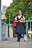 Estudiante femenino Wearing Uniform Walking de la preparación en la acera foto de archivo