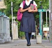 Estudiante femenino Wearing Uniform Walking de la preparación en la acera fotos de archivo