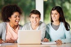 Estudiante With Friends Looking en el ordenador portátil adentro Fotografía de archivo