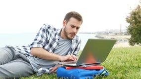 Estudiante frustrado e que aprende con un ordenador portátil en la hierba almacen de metraje de vídeo