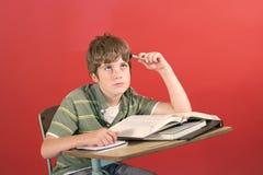 Estudiante frustrado en su escritorio Fotografía de archivo libre de regalías