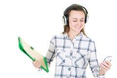 Estudiante Girl que escucha la música de su teléfono con el auricular fotografía de archivo libre de regalías