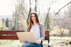 Estudiante Girl que usa un ordenador portátil en un banco en parque cerca de campus Imagen de archivo libre de regalías