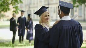 Estudiante graduado que habla con el graduado del varón, sombrero conmovedor, amigos felices almacen de metraje de vídeo