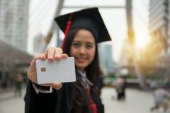 Estudiante graduado que sostiene una tarjeta inteligente en blanco disponible foto de archivo