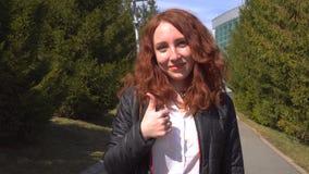 Estudiante hermosa joven del pelirrojo al aire libre en la calle que camina en parque y que muestra los pulgares para arriba almacen de video