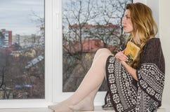 Estudiante hermosa joven que se sienta en un travesaño de la ventana en la ventana que pasa por alto la ciudad y que lee cuidados Imagen de archivo