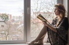 Estudiante hermosa joven que se sienta en un travesaño de la ventana en la ventana que pasa por alto la ciudad y que lee cuidados Foto de archivo