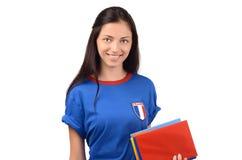 Estudiante hermoso con la bandera de Francia en la blusa azul que sostiene los libros, libro rojo en blanco de la cubierta Foto de archivo libre de regalías