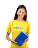 Estudiante hermoso con la bandera de Suecia en la blusa amarilla que sostiene los libros Imagen de archivo