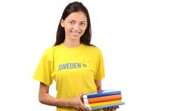 Estudiante hermoso con la bandera de Suecia en la blusa amarilla que sostiene los libros Fotos de archivo