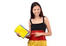 Estudiante hermoso con la blusa de la bandera de Alemania que se sostiene y que señala en los libros. Fotografía de archivo libre de regalías