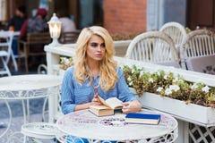 Estudiante hermoso con la mirada asombrosa que se prepara para las conferencias mientras que se sienta con los libros en café Fotografía de archivo libre de regalías