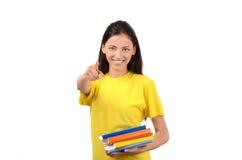 Estudiante hermoso con los libros que señala en frente a usted. Foto de archivo